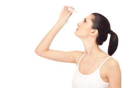 woman dripping eye with eyes drops, isolated on white, close up photo
