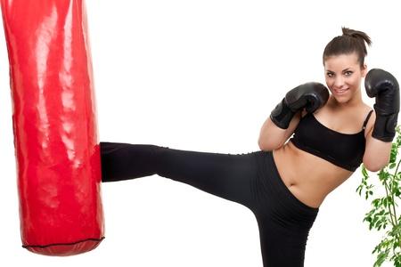 girl punch: female boxer kicking punching bag at home