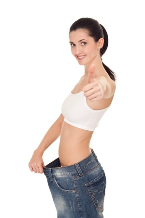 success woman demonstrating weight loss by wearing an old  jeans, with thumb up,  isolated on white Stock Photo - 9175398
