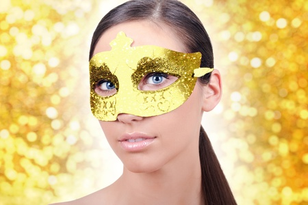 beautiful girl with carnival gold mask on white background photo