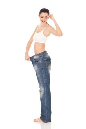 successes: ragazza di successi in grandi pantaloni dopo la dieta, esprimere emozione, su sfondo bianco