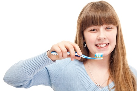 toothbrushing: close up, young girl brushing her teeth happily, isolated on white Stock Photo
