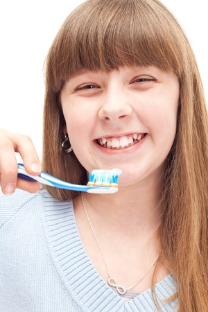 little girl brushing teeth with manual toothbrush, isolated on white photo