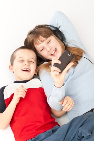 two young children playing on the smart phone photo
