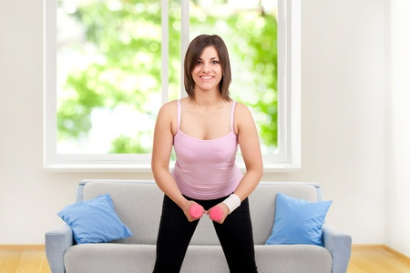 smiling happy woman exercising with dumbbells at home photo