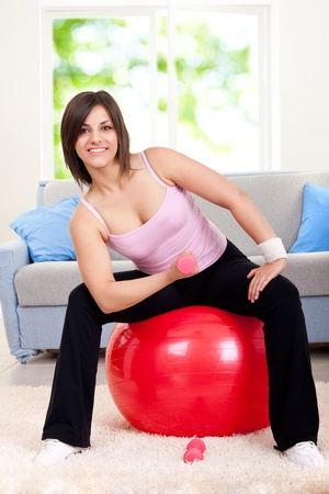 young woman in sportswear, doing fitness exercise with dumbbells on fit ball, indoors photo