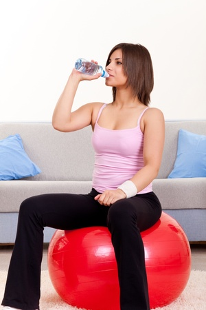 young beautiful woman with bottle of water and gymnastic ball at home Stock Photo - 9228206