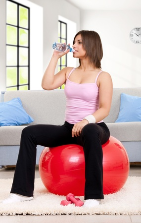 fitness woman on fitness-ball, drinking water at home  photo