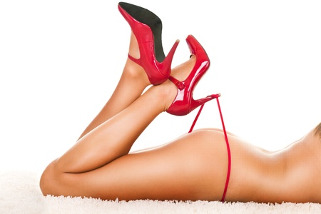 Beautiful woman's legs in heels playing with red panties Stock Photo - 9228237