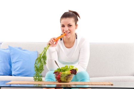 vegetarian teenager sitting on the couch and eating  carrots photo