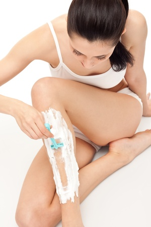 cute woman shaving her legs, isolated on white background Stock Photo - 9319763