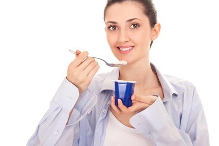 girl eating healthy yogurt for breakfast on white background photo