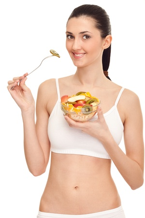 salad fork: fit woman eating fresh fruit salad, isolated on white background
