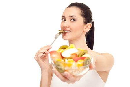 gesunde Woman eating ein St�ck Kiwi aus Salat und stehen, isolated on white background Lizenzfreie Bilder