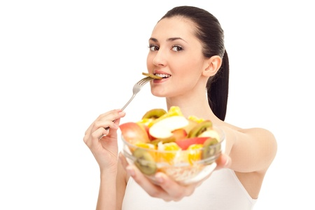 healthy person: healthy woman eating a piece of kiwi from salad and standing, isolated on white background Stock Photo