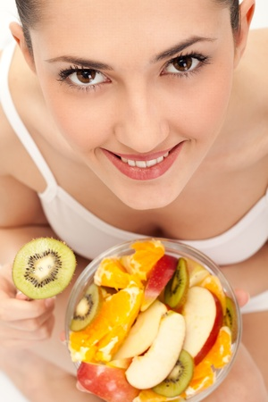 close up, smiling girl eating fresh fruit salad, on white background,  top view photo