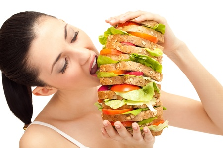 adult sandwich: brunette taking a big bite out of huge sandwich on white background Stock Photo