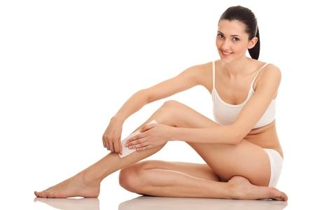 depilacion: mujer haciendo depilaci�n en sus piernas con cera, aislados en blanco