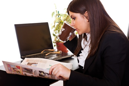 adult magazines: young businesswoman reading the news in newspaper and drinking coffee in her office