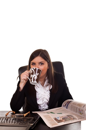 happy businesswoman sitting at table in office, reading newspaper and drinking  coffee,  photo