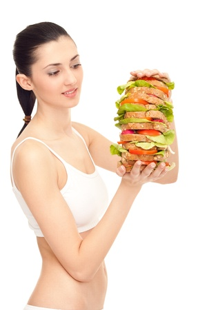 pretty young woman eating big sandwich, isolated against white background photo