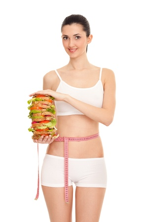 slim woman with measuring tape and big sandwich in arms,  isolated on white photo