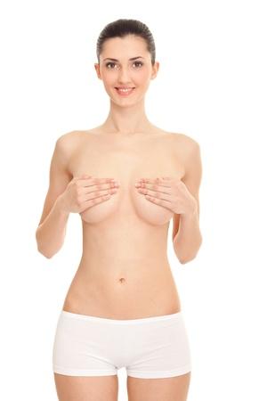 jeune femme nue: nue jeune femme portant sur sa poitrine avec les mains sur fond blanc Banque d'images