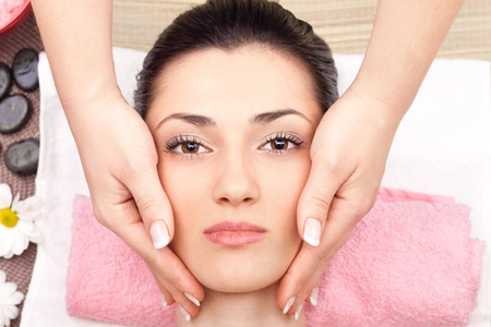 head rest: close up, young cute woman receiving a facial massage, top view Stock Photo