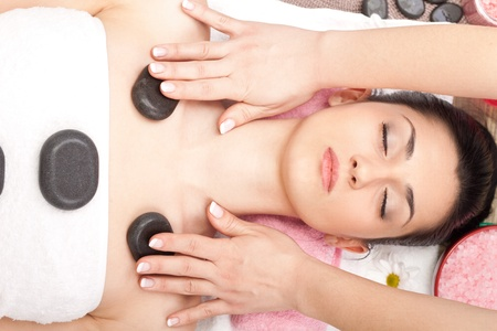 woman getting treatment  with hot mineral stone photo