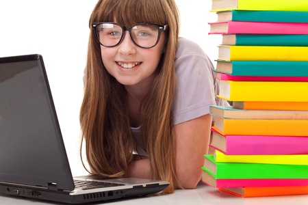 teenager girl between pile of books and laptop, lying on floor, isolated on white photo
