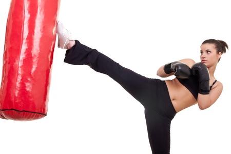 coup de pied: Boxeur de coup de pied de femme avec sac de boxe rouge-isol� sur fond blanc