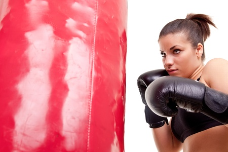 girl punch: girl hitting red boxing bag- isolated on white Stock Photo