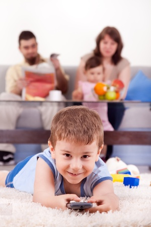 happy family with children sitting on sofa and  watching TV at home Stock Photo - 9438167