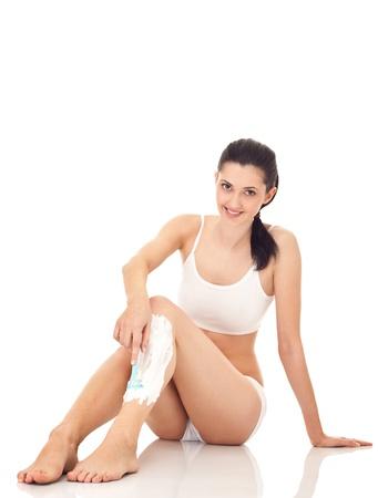 woman in underwear shaving leg, isolated on white Stock Photo - 9438245