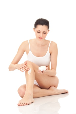 woman putting cream on her leg, isolated on background photo