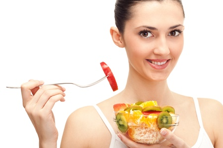 beautiful brunette girl eating fruit salad, close up, isolated on white background photo
