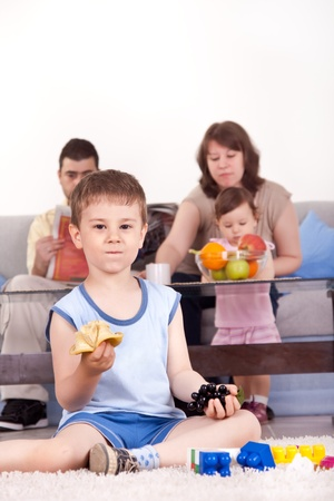 happy family, son eating snack, inside at home photo