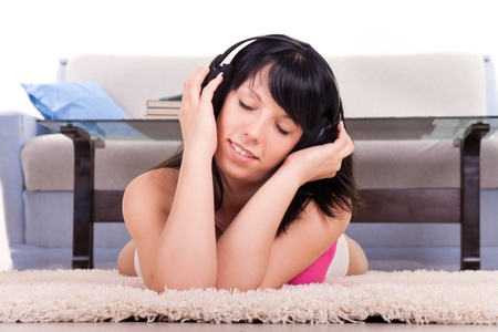 beautiful  girl listens to music through ear-phones at home photo