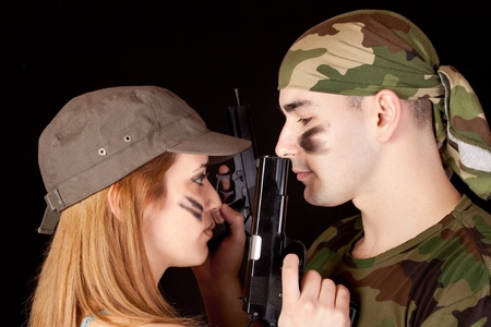 man and woman solders with guns on black background photo