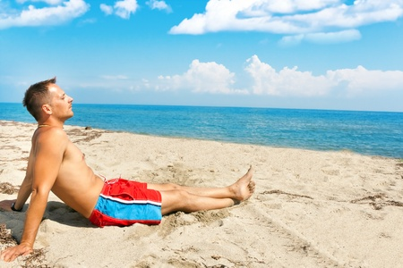 handsome man enjoying in sun on the beach photo