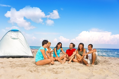 camping equipment: group young people camping together on beach Stock Photo