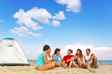 camping equipment: happy young friends camping on beach next tend