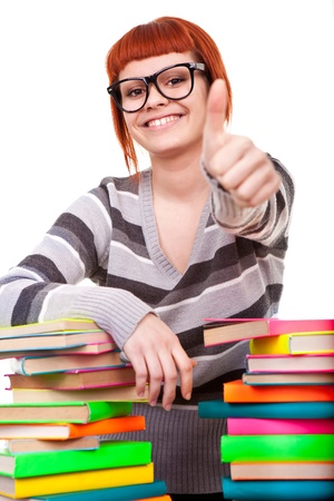 girl with pile book showing thumb up, isolated on white background photo