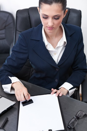 shorthand: young businesswoman sitting at the desk in office and stamping document Stock Photo
