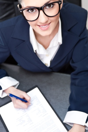 smiling businesswoman making note, top view photo