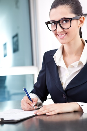 smiling businesswoman taking notes in office Stock Photo - 9569235