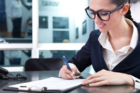 smiling businesswoman signing a contract in office Stock Photo - 9569295