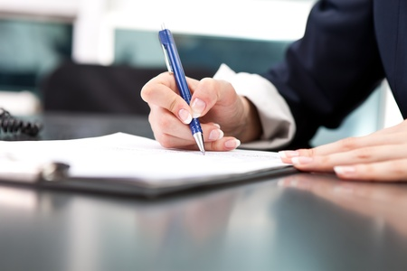pen: womans hand with pen signing document, close up Stock Photo