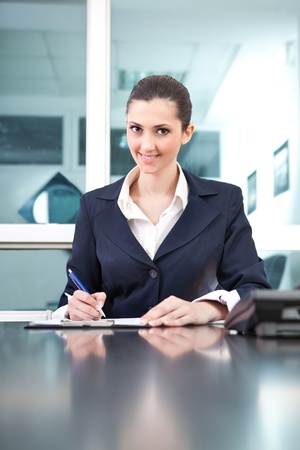 smiling businesswoman sitting on desk in office Stock Photo - 9565344