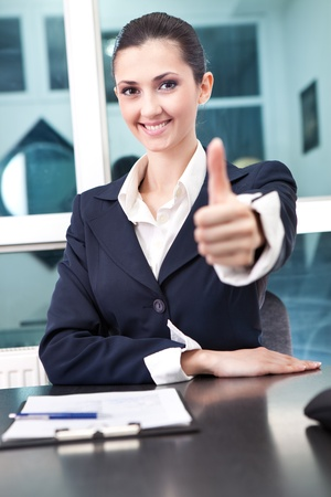 portrait of a happy young businesswoman showing thumb up sign photo
